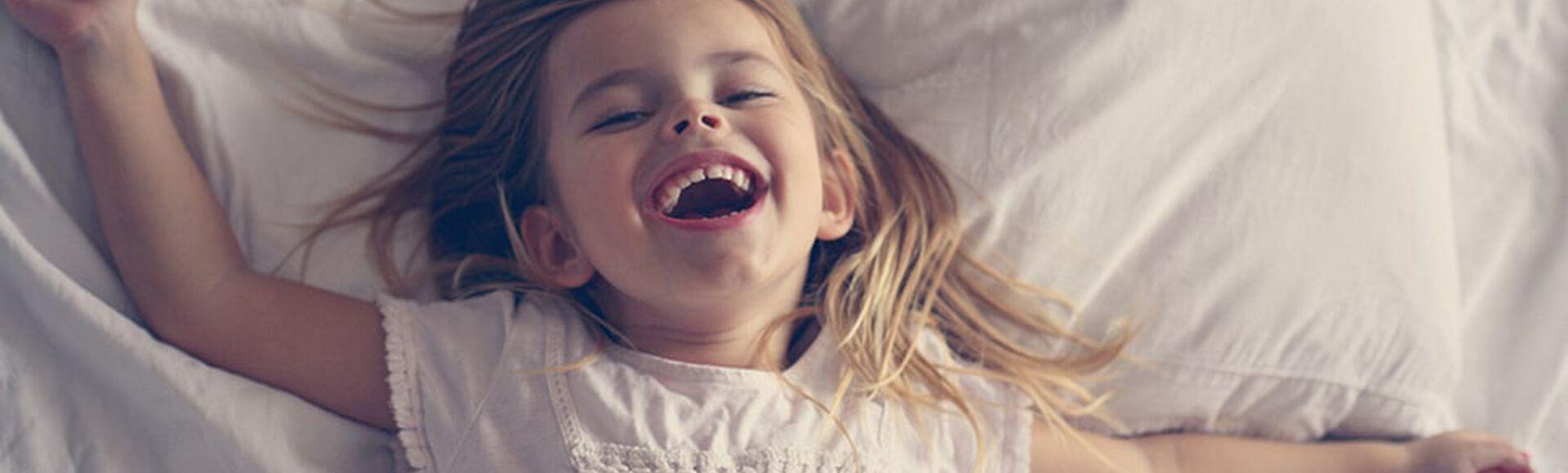 Niña feliz acostada en la cama